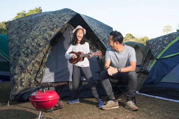 Pai filha, em, acampamento, tocando, ukulele