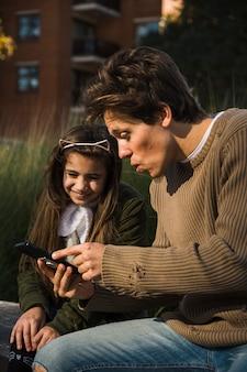 Pai filha, olhar, telefone móvel, tela, enquanto, sentando, parque