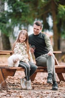 Pai filha, tocando, com, cão, ao ar livre
