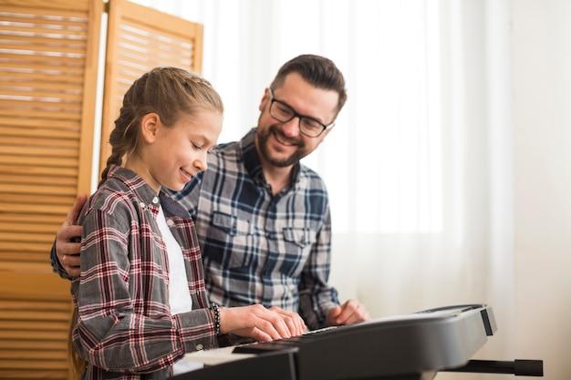Pai filha, tocando, piano