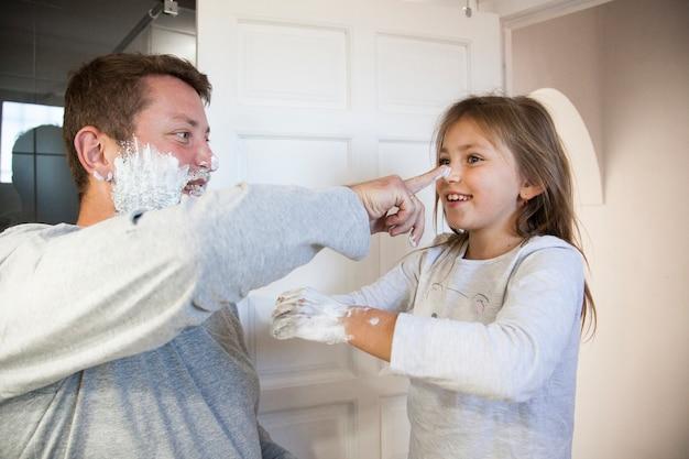 Pai, filha, tocando, raspar, espuma