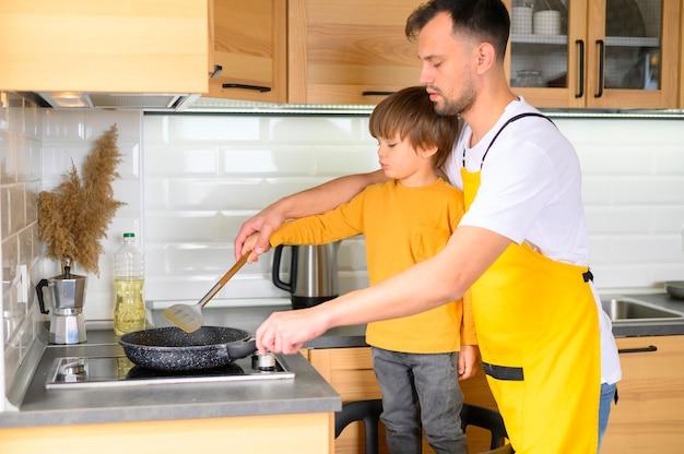 Pai filho, cozinhar, vista lateral