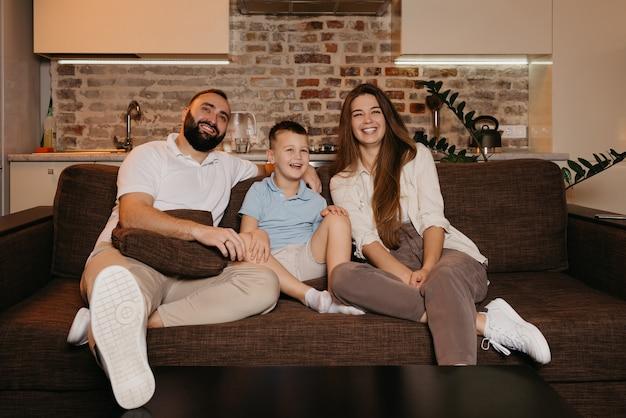 Pai, filho e mãe estão assistindo tv com interesse e rindo no sofá do apartamento