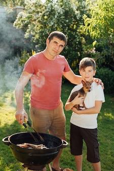 Pai filho, olhando câmera, durante, cozinhar, ligado, churrasco, parque