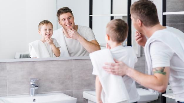 Pai filho, olhando espelho, tocar, seu, queixo, com, mãos