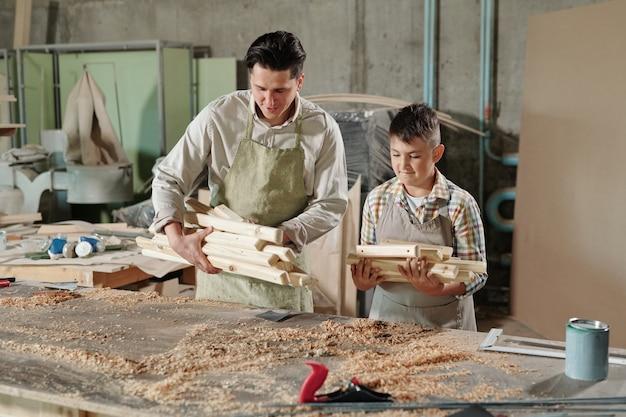 Pai habilidoso de avental, colocando pranchas de madeira na mesa enquanto se prepara para trabalhar em madeira com o filho na carpintaria