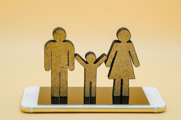 Pai homem, mulher e criança ícone de madeira no telefone inteligente.