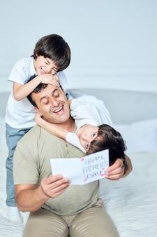 Pai incrível, irmãos de meninos latinos abraçando o pai e dando a ele um cartão postal feito à mão parabenizando