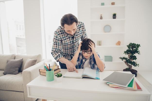 Pai inteligente, inteligente e paciente ajudando seu filho confuso e assustado a se preparar para o exame