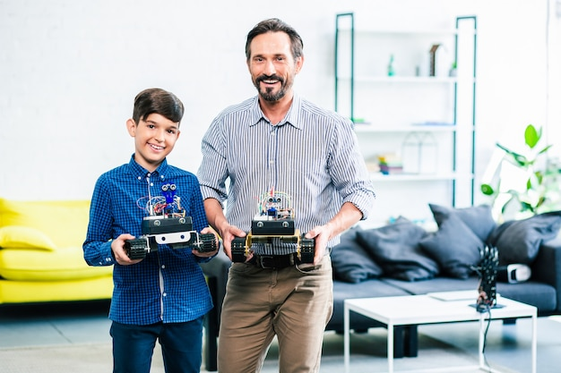 Pai inteligente positivo e seu filho engenhoso segurando dispositivos robóticos enquanto os apresenta para a competição
