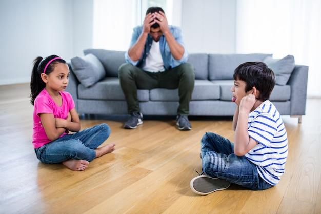 Pai irritado, sentado no sofá enquanto crianças brigando