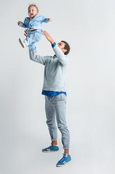 Pai jogando seu filho no ar. família feliz.