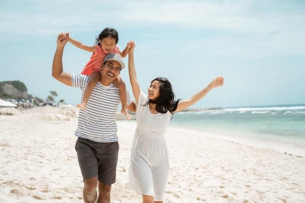 Pai jovem asiático carregando sua filha nas costas
