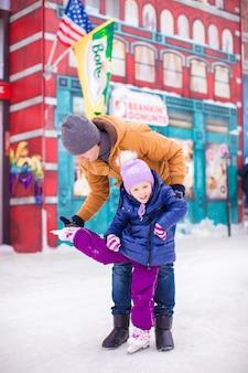 Pai jovem e adorável menina se divertir na pista de patinação