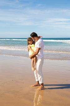 Pai jovem e bonito passando tempo de lazer com a filha na praia, no mar, segurando a criança nos braços