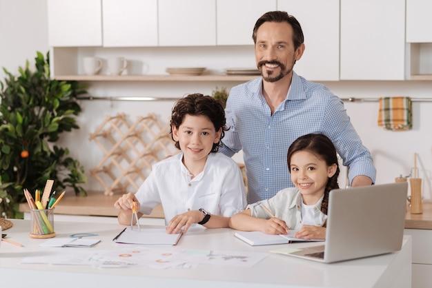 Pai jovem e encantador abraçando seus filhos adoráveis por trás, enquanto seu filho usando uma bússola e sua filha fazendo anotações e todos eles olhando para frente com sorrisos sinceros