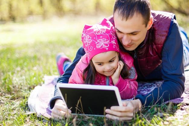 Pai jovem e fofa filha lendo no parque de verão