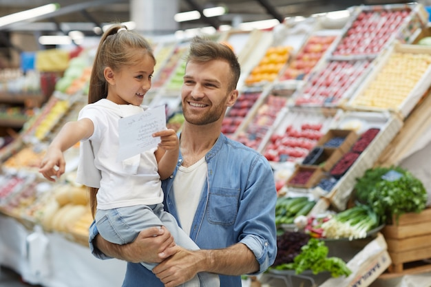 Pai jovem feliz no supermercado