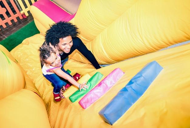 Pai latino-americano brincando com filha mestiça em escorregador inflável na sala de jogos do jardim de infância