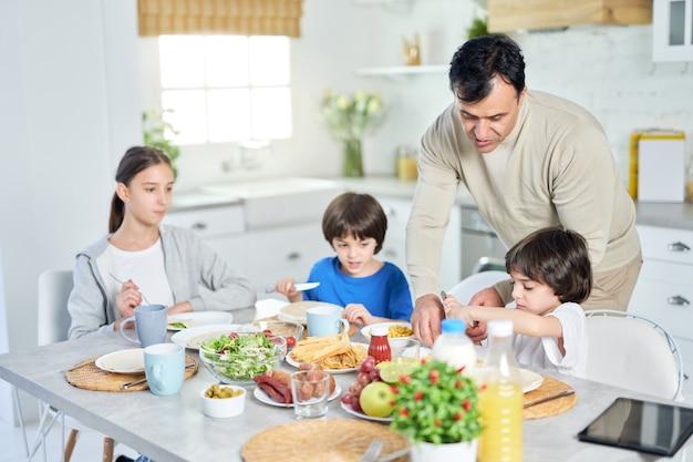 Pai latino amoroso servindo seus filhos pequenos enquanto tomamos café da manhã juntos em casa. infância, paternidade, conceito de cozinha latina