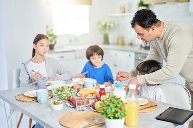 Pai latino carinhoso servindo seus filhos adoráveis enquanto tomam café da manhã juntos em casa. infância, paternidade, conceito de cozinha latina