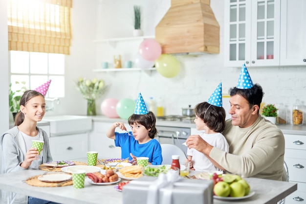 Pai latino de meia idade amoroso com crianças usando bonés de aniversário na cabeça e jantando enquanto comemorava aniversário juntos em casa. paternidade, conceito de família feliz
