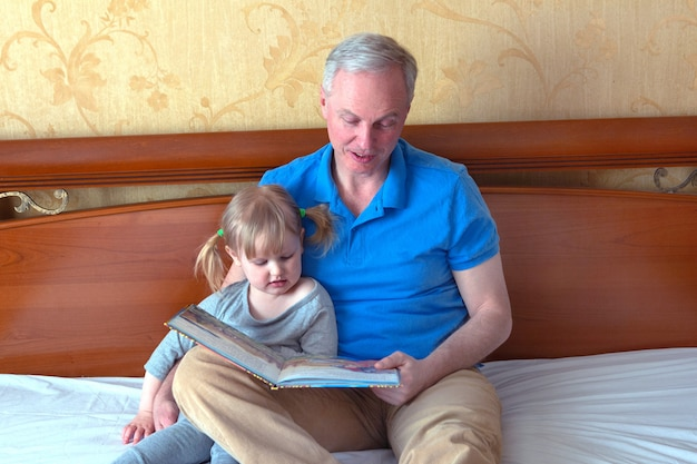 Pai lê livro de filhas enquanto estava deitado na cama