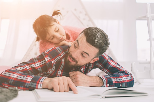 Pai lendo um livro para sua filha enquanto estava deitado no chão no quarto. filhinha e seu pai jovem e bonito estão brincando juntos no quarto da criança.