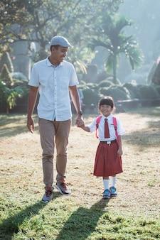 Pai leva seu filho para a escola pela manhã