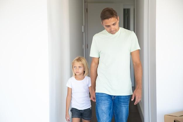 Pai levando a filha de cabelos louros para o novo apartamento, segurando a mão, andando no corredor