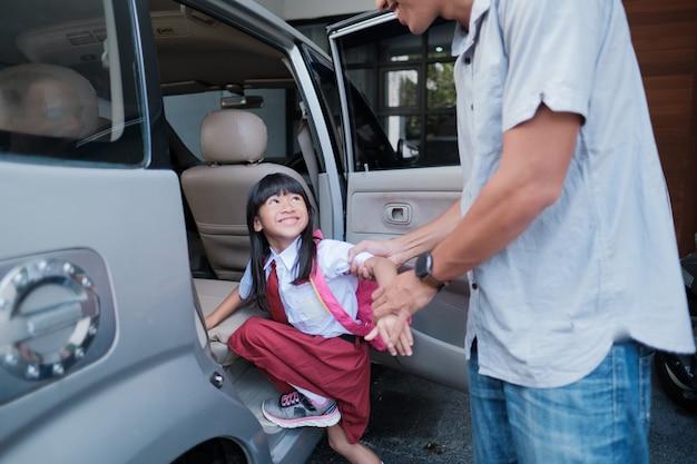 Pai levando a filha dela para a escola pela manhã, dirigindo um carro. aluno primário asiático de volta à escola