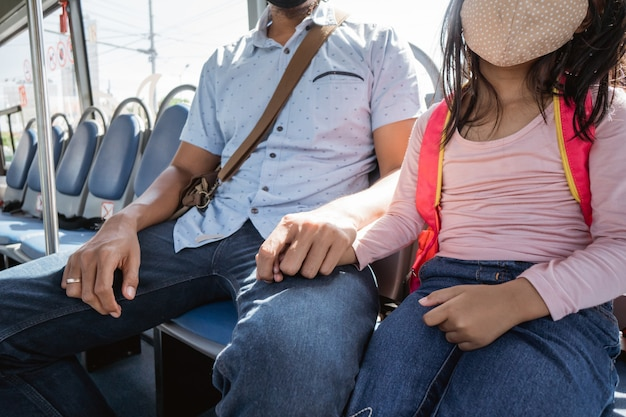 Pai levando a filha para a escola no ônibus e segurando a mão