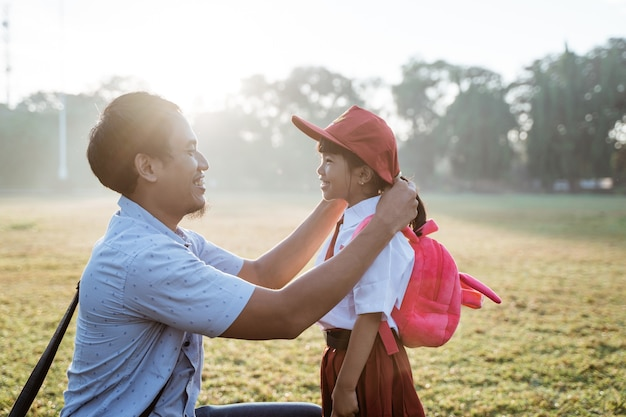 Pai levando a filha para a escola primária pela manhã