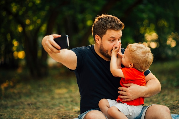 Pai, levando, um, selfie, e, tocando, com, seu, criança