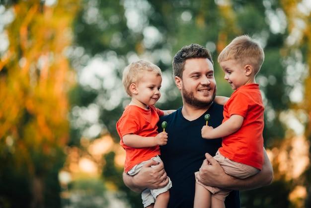 Pai, levantando seus filhos com os dois braços