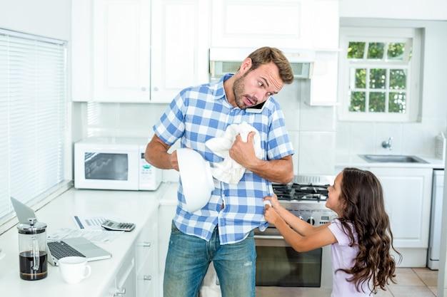 Pai limpando recipiente enquanto filha puxando-o