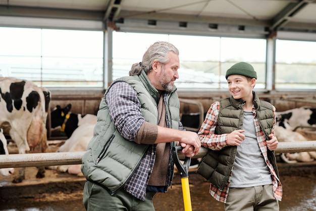 Pai maduro positivo e seu filho apoiados na grade da baia e discutindo sobre o gado durante o intervalo na fazenda
