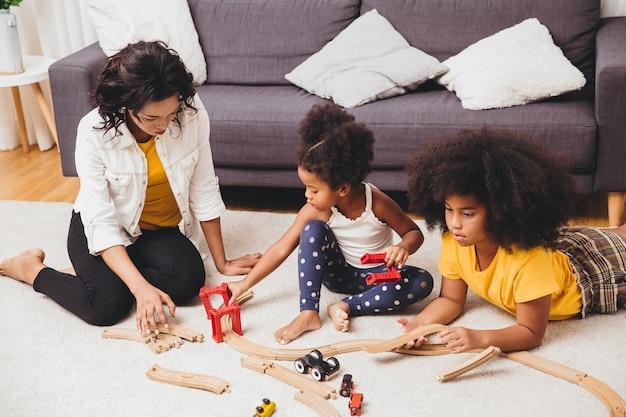 Pai mãe brincando com as crianças aprendendo a resolver o brinquedo do quebra-cabeça no apartamento de casa. babá procurando ou cuidando de crianças negras na sala de estar.