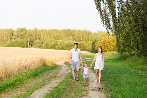 Pai, mãe e bebê estão andando na estrada perto do campo