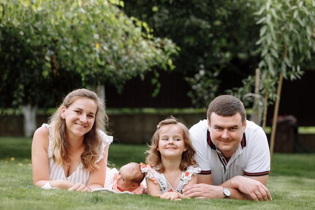 Pai, mãe e dois filhos, menina e filha na grama em dia de verão