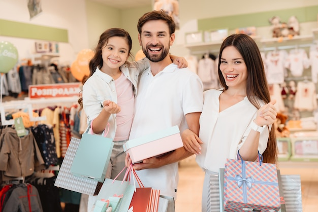 Pai, mãe e filha estão na loja de roupas