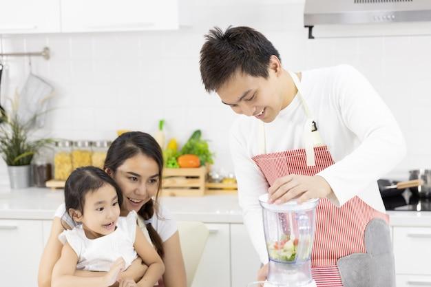 Pai, mãe e filha estão preparando o almoço