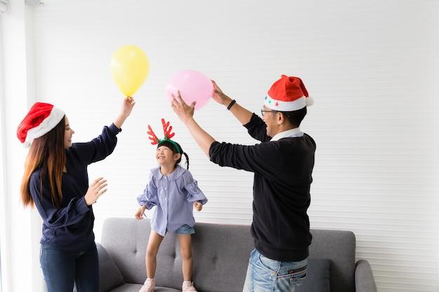 Pai, mãe e filha jogando balões na sala. eles sorriem e estão felizes.