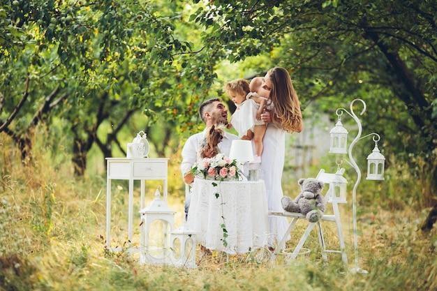 Pai, mãe e filha juntos no piquenique no jardim