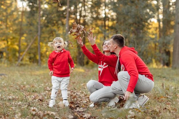 Pai, mãe e filha se divertindo e brincando no parque outono.
