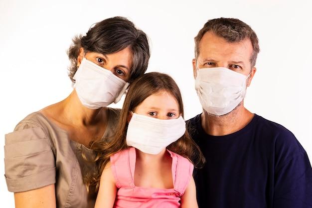 Pai, mãe e filha usando máscaras protetoras em fundo branco