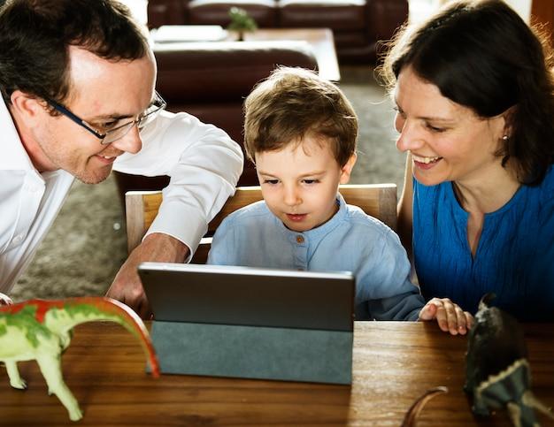 Pai mãe e filho assistindo tablet passar o feriado de tempo juntos