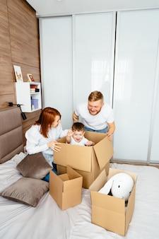 Pai, mãe e filho brincam no quarto com caixas de papel