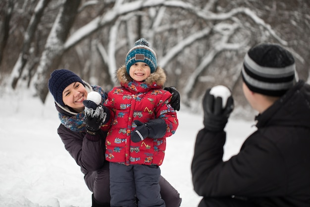 Pai, mãe e filho brincando em bolas de neve em winter park