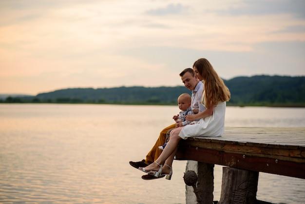 Pai, mãe e filho de um ano se divertem na natureza perto do lago.